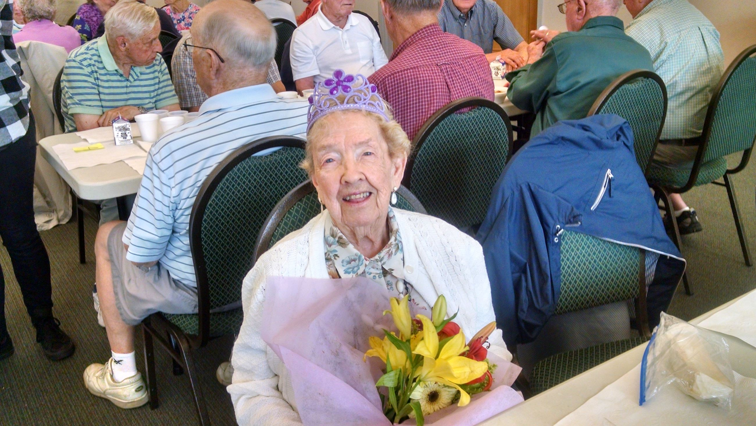 A woman wearing a purple tiara celebrates her 100th birthday at the COA Wednesday Lunch.
